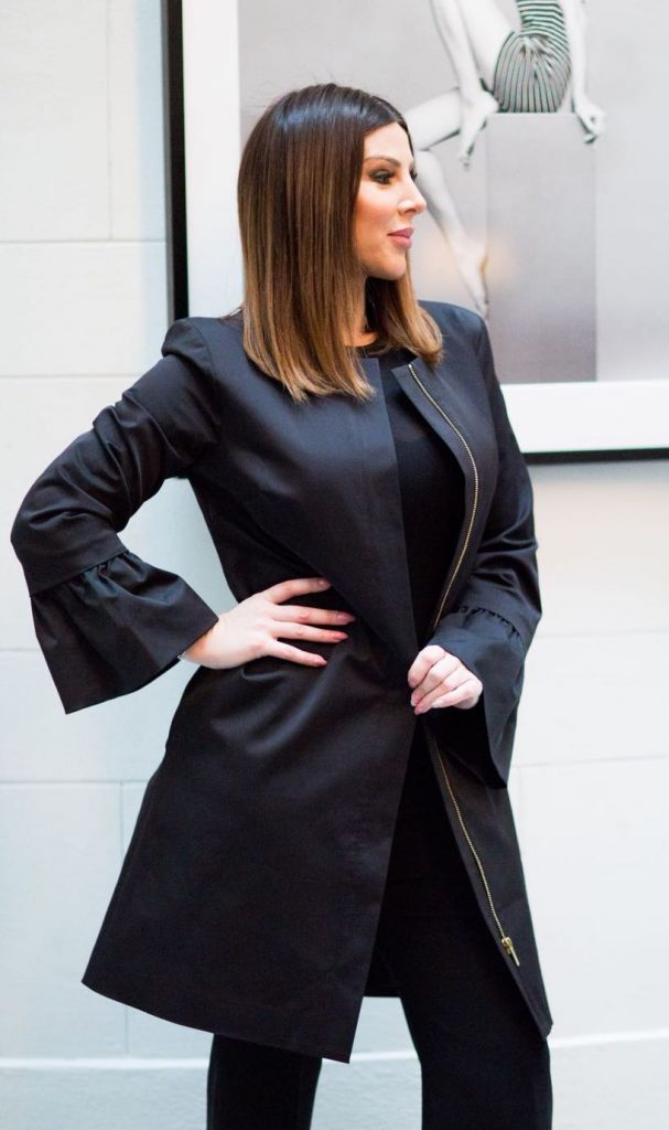 The black female coat with bellcuff sleeves